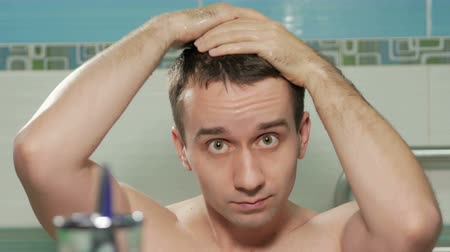 tüy : Young attractive man straightens hairstyle after a shower in the bathroom of the hotel room. He hands combs hair in the desired direction. He is looking at the camera in the mirror. Stok Video