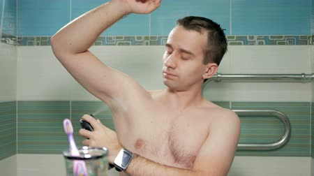 antiperspirant : A young attractive man gets antiperspirant spray in the bathroom of the hotel room. He smiles and frowns of the strong smell. He is looking at the camera in the mirror.