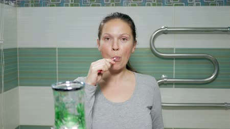 kartáč : A young attractive woman brushing her teeth in the bathroom of the hotel room. It causes the paste on the brush and looking at the camera