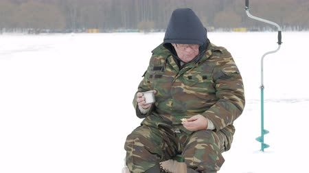 fishermen : A man fishing on the lake in winter and drinking tea from a flask. He eats biscuits with a hot drink Stock Footage