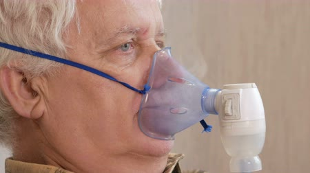 akciğer : An elderly man holding a mask from an inhaler at home. Treats inflammation of the airways via nebulizer. Preventing asthma and cough. Close-up. Stok Video