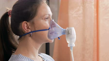 rekedt : Young woman holding a mask from an inhaler at home. Treats inflammation of the airways via nebulizer. Preventing asthma and cough