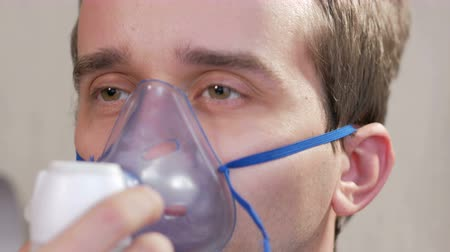 oksijen : Young man holding a mask from an inhaler at home. Treats inflammation of the airways via nebulizer. Preventing asthma and cough