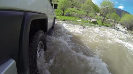 ралли : Jeep rides through the river in the woods slow motion Стоковые видеозаписи