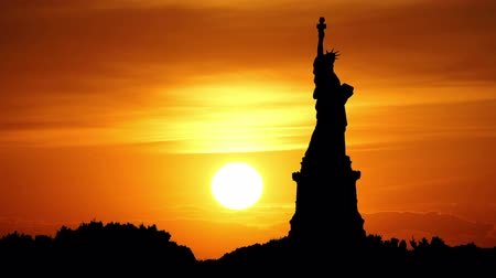 статуя : Sun goes behind Statue of Liberty, New York, USA