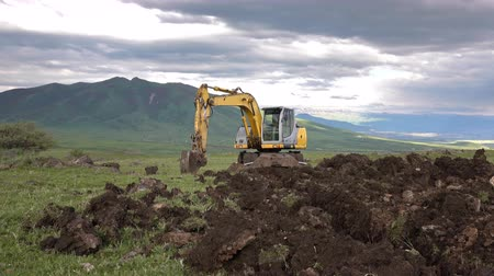 escavador : Dolly shot of the excavator digging hole on the mountainous landscape Stock Footage