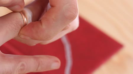 hurl : white male forcefully takes from his finger a gold wedding ring and throws it on the torn red cover. the concept of divorce, rupture of relations. selective focus Stock Footage