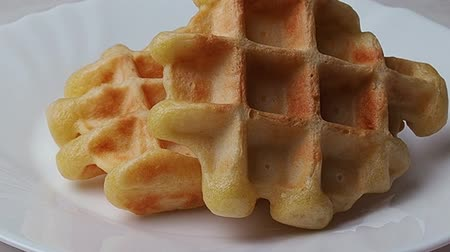 Belgian waffles in a white plate on a light background. Waffles without filling.