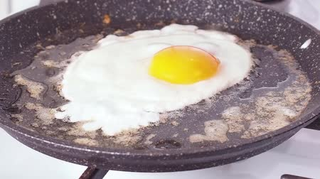 Fried eggs fried in a frying pan Стоковые видеозаписи