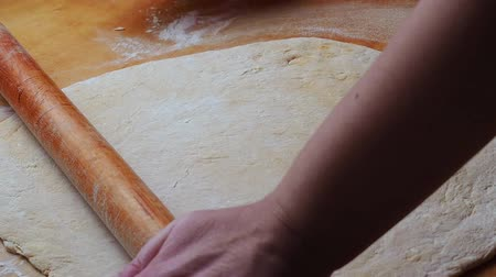 Woman rolls dough close up