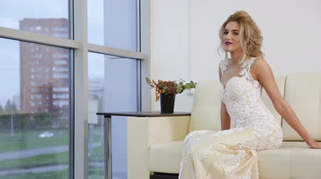 slowing : Bride sitting near a window on the couch. Stock Footage