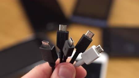 cabling : A heads of a standard Micro USB plug, a several smartphones visible on the background.