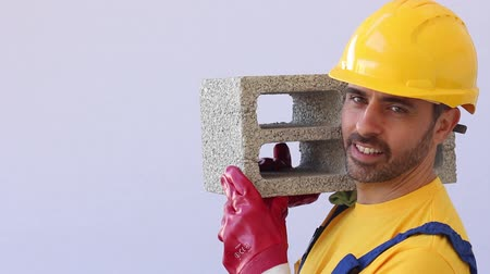 безопасный : construction worker lifting heavy block