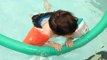 yüzme havuzu : Child swimming in a swimming pool wearing floating armbands