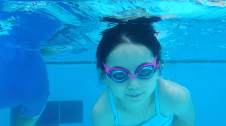 swimming underwater : Underwater shot of young girl swimming and diving