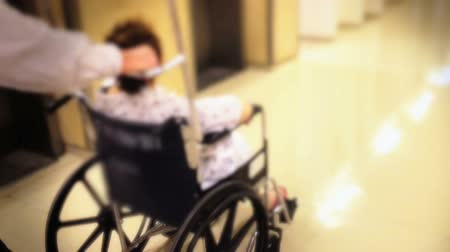 toló : Shot of Carrying woman in wheelchair around the hospital