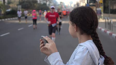 kilometer : Shot of Girl taking pictures of marathon runners