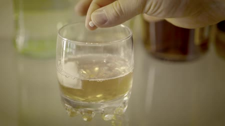 sedative : Shot of Close up of hand putting drug in drink Stock Footage