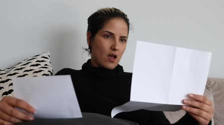 letras : Sad and shocked woman reading a letter on a couch