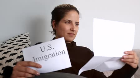 illegal alien : Woman sitting on couch reading USA immigration papers Stock Footage