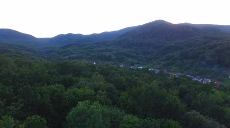 sunrice : View from the birds-eye view at sunrise in mountain woodland. Video with copter which flies out of the hill and overlooks the small village in the valley.