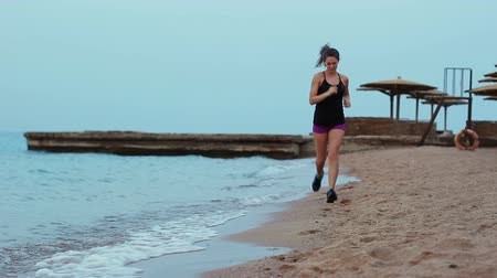 The sports girl runs along the sandy beach on which the waves roll. Brunette doing a morning jogging on the coastline.