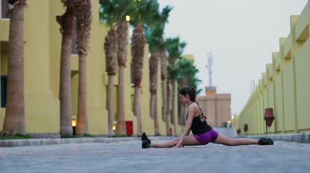 A sporty young woman sits on a twine in the background of beautiful residential buildings. Brunette looks at the camera performing an exercise.