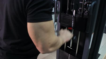 The athlete pumps the muscles on the simulator by lifting the big weight up. Male triceps close-up.