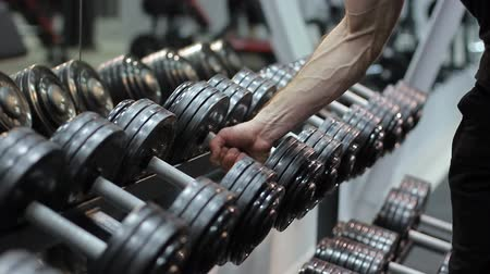 The athlete approaches the shelf with dumbbells and takes one of them and then leaves engaged. A large number of sports equipment. Стоковые видеозаписи