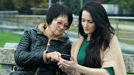A young daughter is teaching her mother how to use a smartphone. Two brunettes of different ages are sitting on a bench.