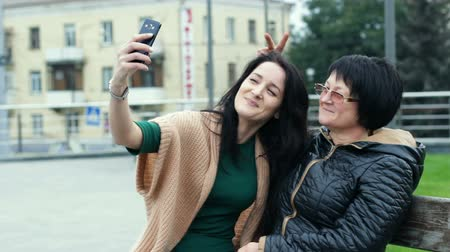 Mom and daughter are having fun together while making selfies on a smartphone. An adult woman depicts horns on a young girl.