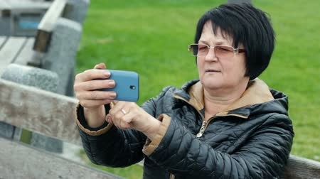 Woman tries to make selfie and is very happy about it. Funny adult brunette with a smartphone in her hands.