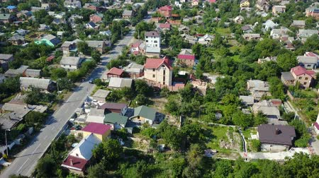 yoğunluk : Video from the drone. View from high to a car that rides along an asphalt road in a small suburban village. The camera moves down above the roofs of houses.