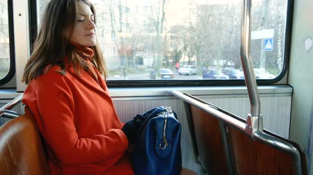 Cute girl in an orange coat and carrying a blue bag goes in public transport. Brunette looks through the tram window and then at the camera and is embarrassed.