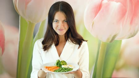 otimista : Pretty girl in a white robe holds a large plate of boiled vegetables and pushes it forward. Healthy and proper nutrition. Vegetarian food.