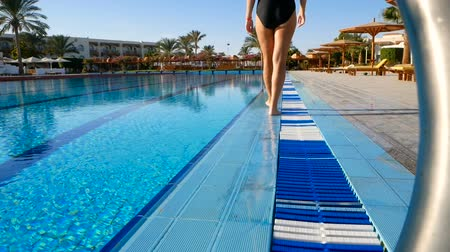 A young woman with slender legs and a good figure slowly walks along the pool for a sports swim. Beginner swimmer after the swim. Стоковые видеозаписи
