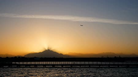 The plane flies over the sunset over the mountains. Rays of light pass through the evening mist. Calm sea and pier in the foreground.