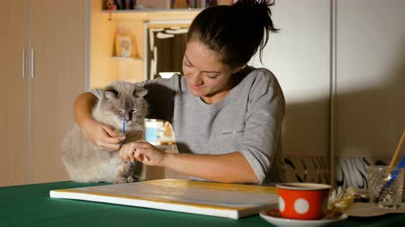 Beautiful girl play with her pet. A young artist tries to teach a cat to draw. Owners and their funny animals. Стоковые видеозаписи