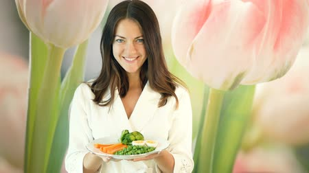 Pretty girl in a white robe holds a large plate of boiled vegetables and pushes it forward. Brunette winks. Healthy and proper nutrition. Vegetarian food. Стоковые видеозаписи