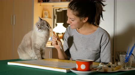 Girl artist play with his pet with a brush for drawing. Brunette spends her leisure time with the cat.