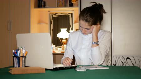 Girl dressed in a white blouse is working at home behind a laptop. Journalist looks at the screen and is very nervous that she does not succeed. Стоковые видеозаписи