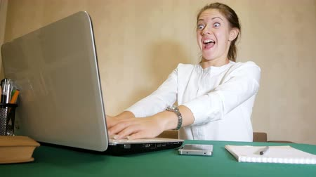 Young woman very quickly typing on a laptop with a facial expression like mad. Heavy work of freelancer.