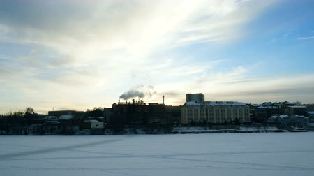 Panoramic video overlooking the winter city on the river. From the chimney of the plant comes thick smoke.