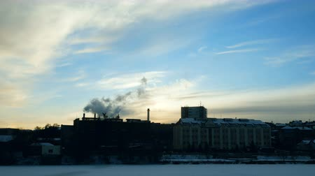 Timelapse video overlooking the winter city on the river. From the chimney of the plant comes thick smoke. Pollution of the environment.