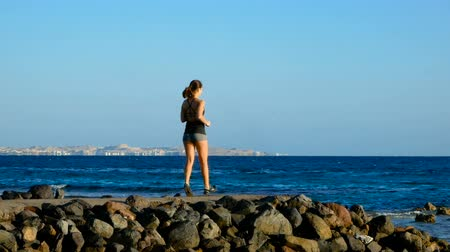 Sports girl running along the stone path to the sea. Brunette looks away and dreams.