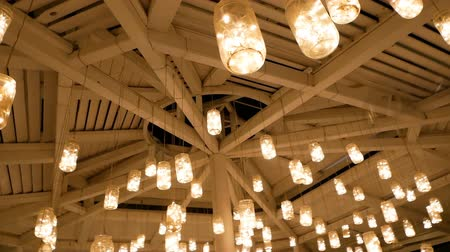 Self-made lanterns from cans are suspended on a wooden ceiling and shine brightly. Camera moves around the fixtures and the ceiling fan.