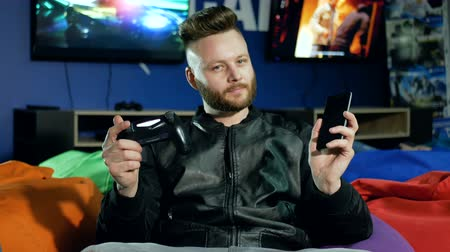 решить : Young man with a beard holds a smartphone and a joystick in his hands and can not decide what to play. Стоковые видеозаписи