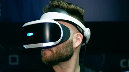 grãos : Bearded guy in virtual reality glasses turns his head.