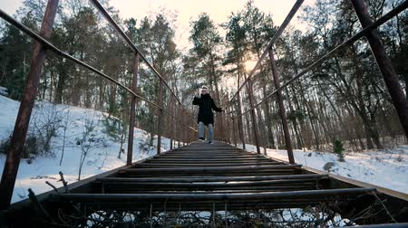 sztafeta : Novice blogger filming himself using a smartphone and a device to stabilize the video. Stylishly dressed man climbs down the steps in the forest. Wideo