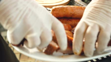 barbecue set : Cook shifts the ready-made pork ribs from the cutting board to a plate with sauces and sausages. Stock Footage